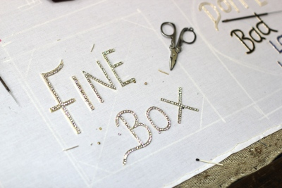 Sanika's designs for the fine box badges being hand embroidered